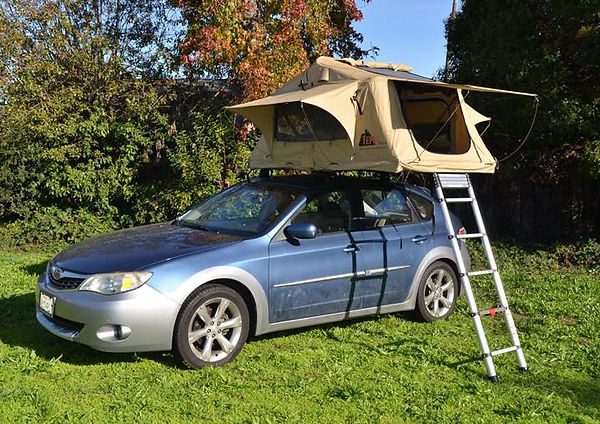 Beige tent with ladder on top of blue car