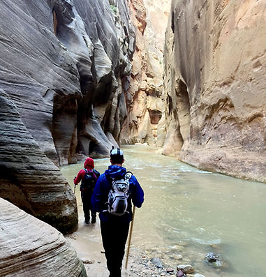 two people walking through flooded slot canyon