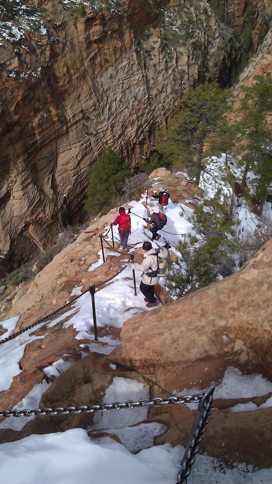 Four people descending steep and snowy red rock slope