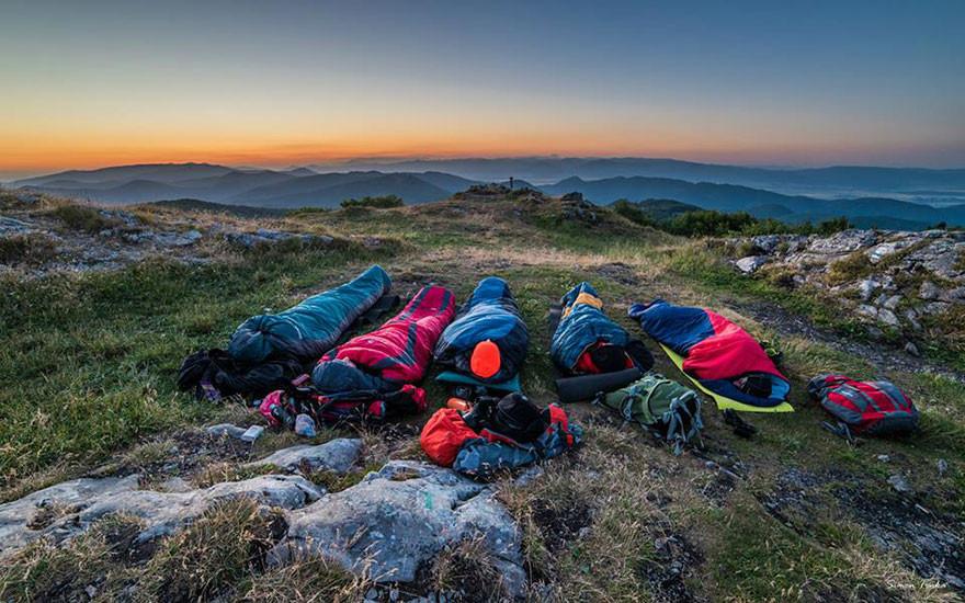 five people in sleeping bags outside
