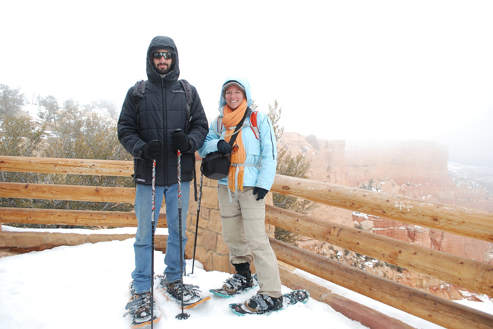 A man and a woman on snowshoes posing for a photo at viewpoint
