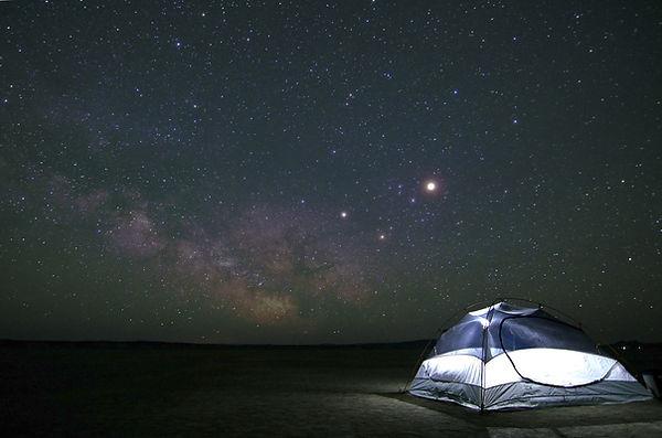 Lit tent under starry skies