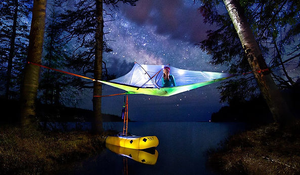 green tent under starry skies strung between two trees over body of water with ladder going down to yellow boat