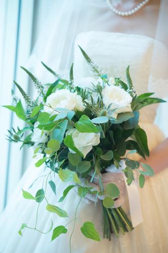 色々なグリーンにシンプルに白いバラだけを合わせたクラッチブーケ。持っているだけで躍動感を感じるようなブーケです。