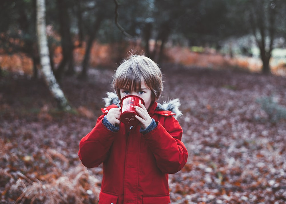 A child outdoors with a mug