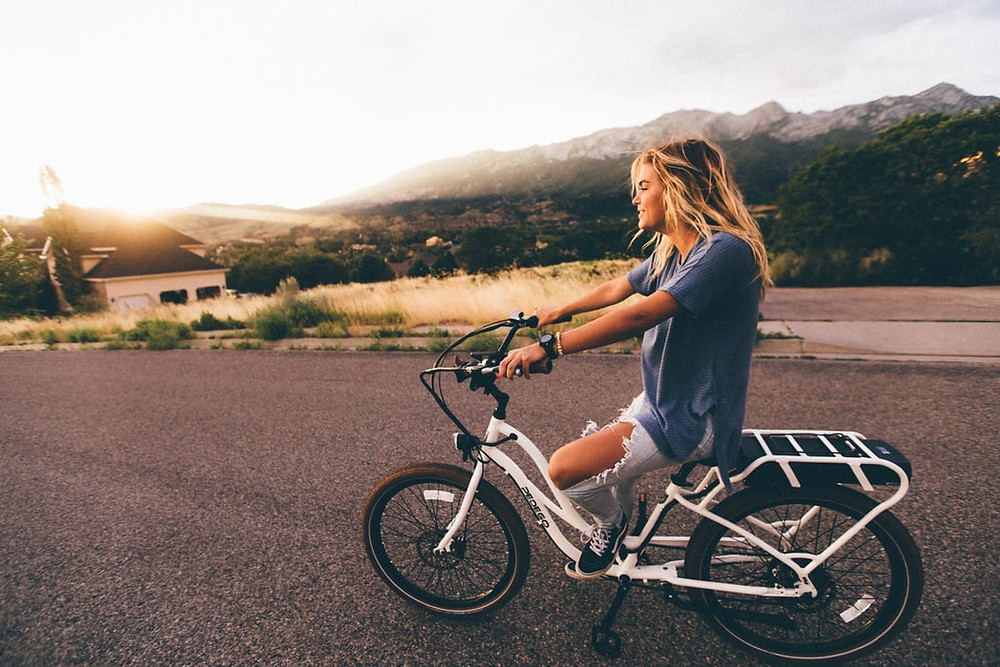 Young woman rides a bike to sunset