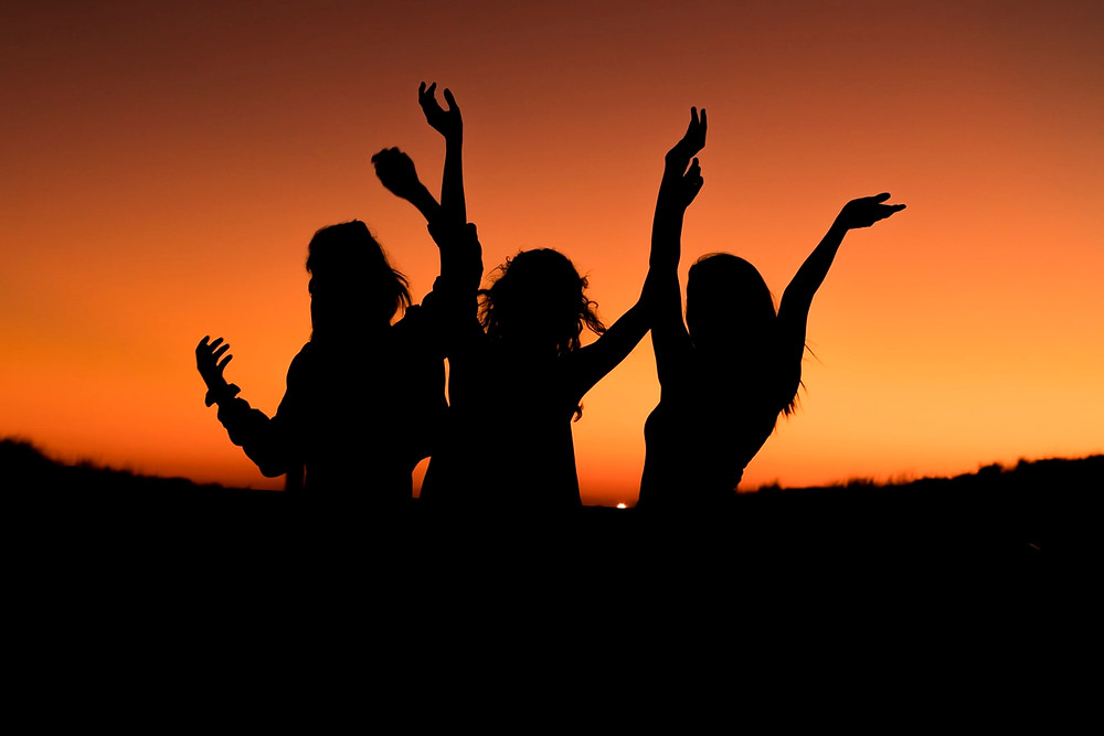Three girls dancing in the setting sun