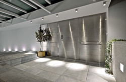 Pivot Door covered with stainless steel insets and wall cladding made of the same material...