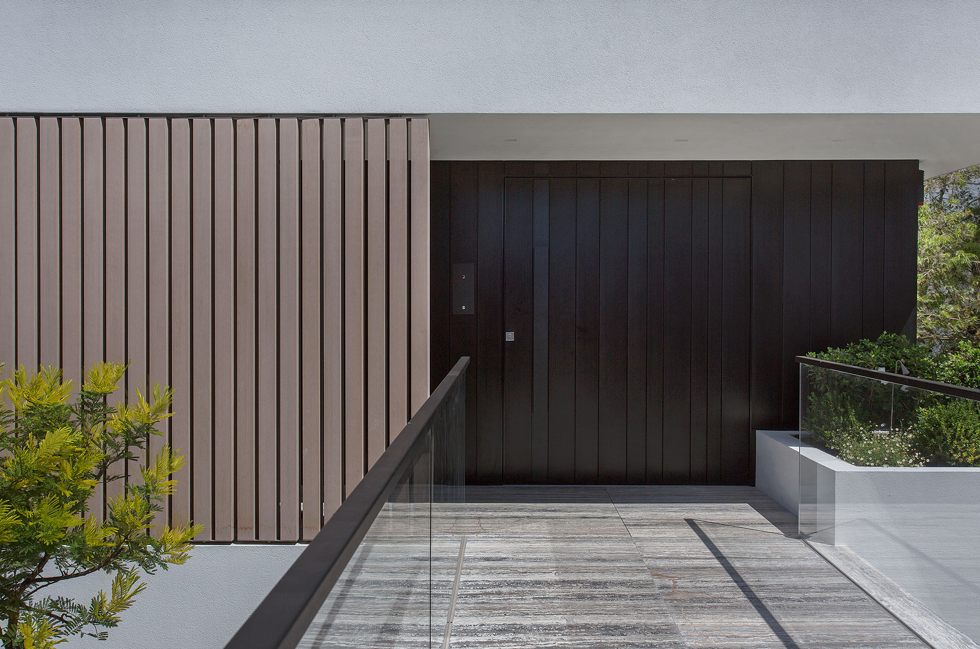 Pivot Door Covered With Vertical Aluminum Insets. Wall Cladding Made With The Same Material
