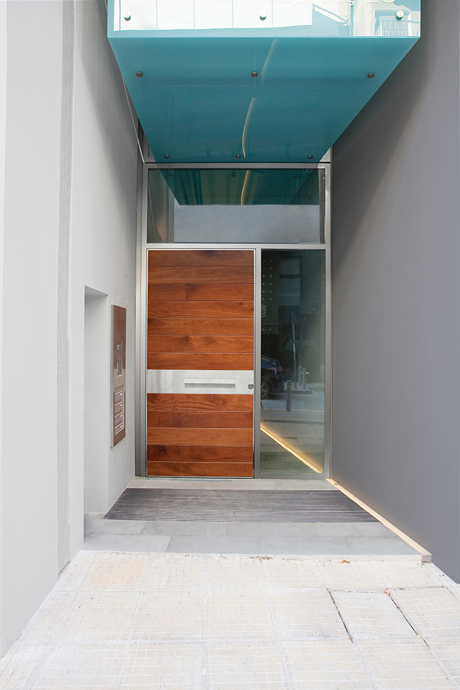 Pivot Door covered with iroko wood and steady side parts made of glass