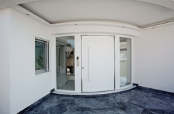 Curved Pivot Door covered with Corian and curved side parts made of glass. Handle made of Corian and