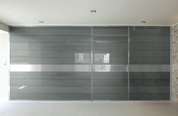 Pivot Door covered with glass insets and wall cladding made of the same material..