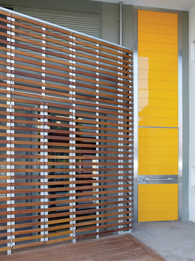 Pivot Door covered with glass insets and upper steady part made of the same material.