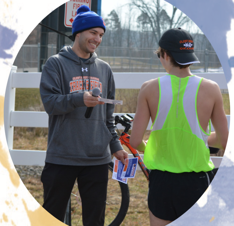 Track and field coach Adam Walters hands a student runner his prize at the annual 5k held by the track and field team. Photo credit by Maeve O'Boyle & Maddie Fuller