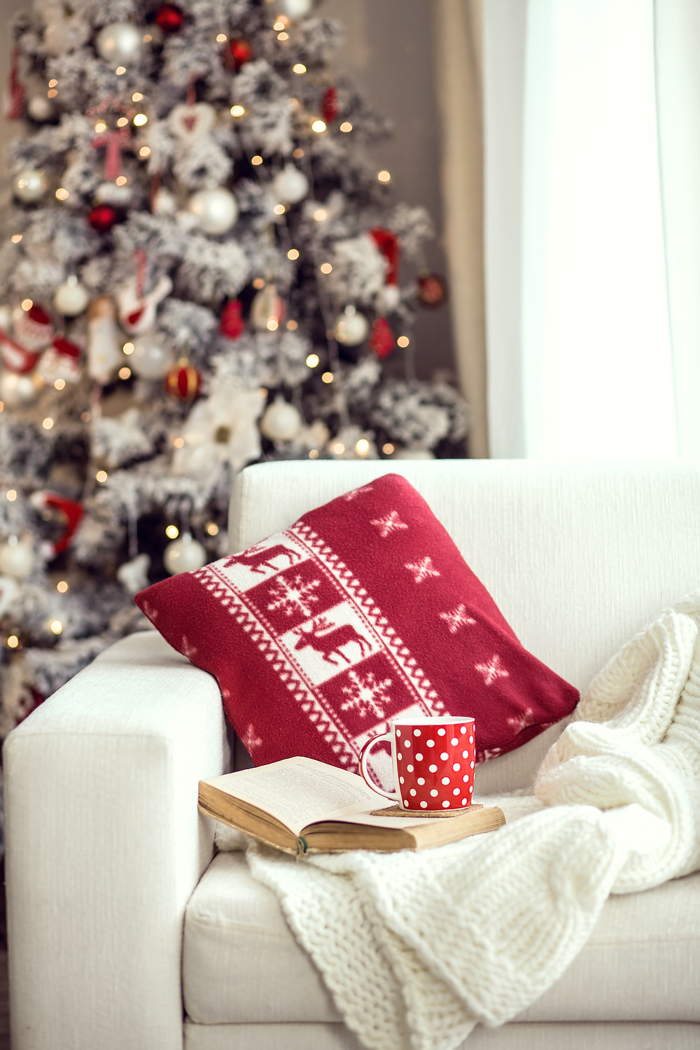 Cozy holiday scene of a tree, a book and a cup of coco.