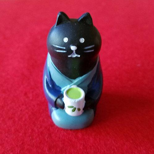 Black cat drinking green tea