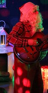 Le Père Noël chante une chanson accompagné par sa guitare