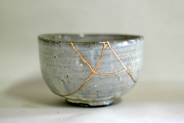 A cracked, grey bowl, repaired in the kintsugi style using gold to fill in the cracks.
