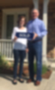 Kim and Mike Ward are standing in front of their Pointe Marin Novato home, just sold by Team McGinnis Novato Realtors