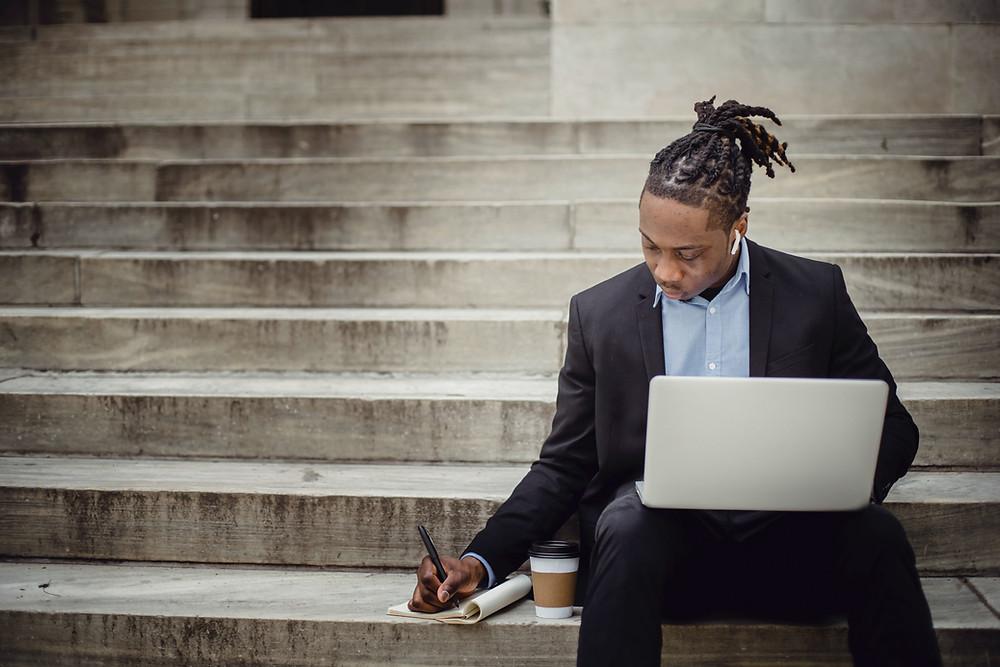 Black man is writing in a notebook near a bridge.