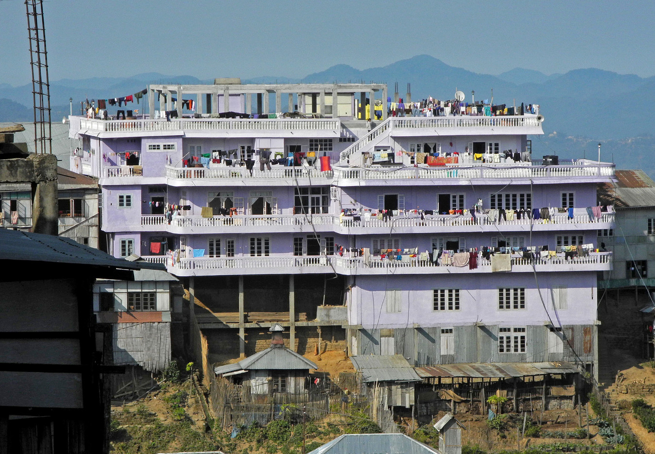The multi-storey house sits on the side of a mountain.