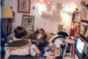 "JEF BRETSCHNEIDER: 1980-81 Jef Bretschneider with a guest at 23rd street loft. Note: Two Basquiat oil stick drawings share the wall with ""Shifting Borders"" . Sitting across from Jef is the cinematographer, Lisa Rinzler; Pollack, Menace 2 Society, Dead Presidents, Trees Lounge, etc."