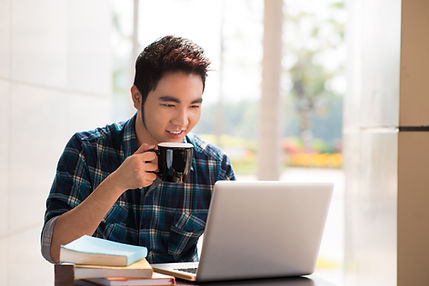 Image of a young guy drinking coffee whi