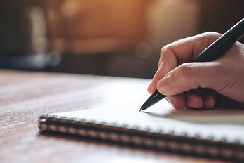 Closeup image of a hand writing down on