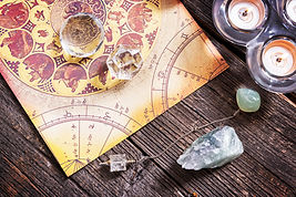 Zodiac chart stylzed with pendulum on a wood table with candles