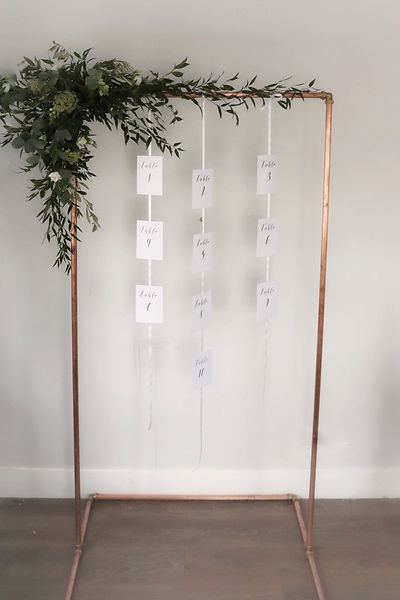 Industrial copper pipe wedding table plan backdrop