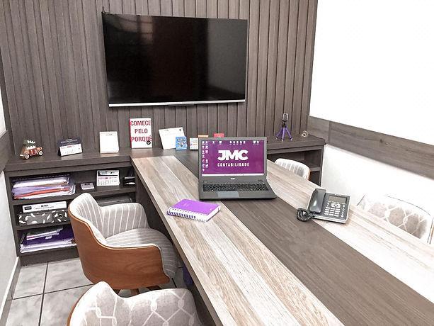 Uma sala de reunião com uma mesa central, uma televisão presa na parede e livros na estante