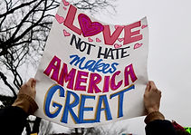 """Protestor holds up a sign that reads, """"Love, not hate, Makes America Great"""""""