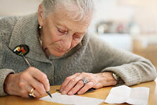 An elderly woman writes a letter to her representative at her kitchen table