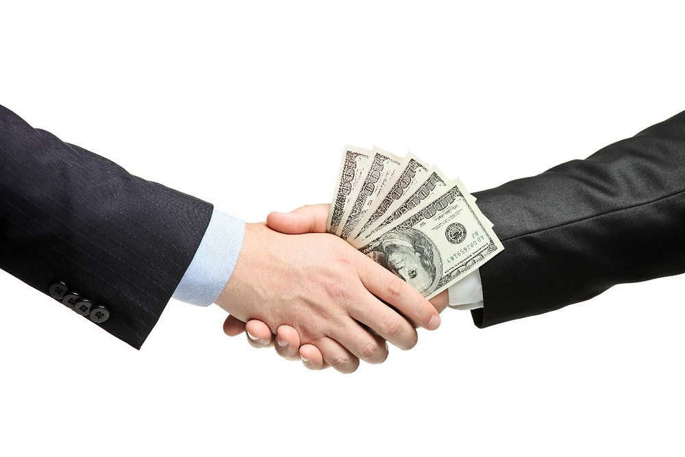 A picture of a bribe taking place between a lobbyist and a politician.