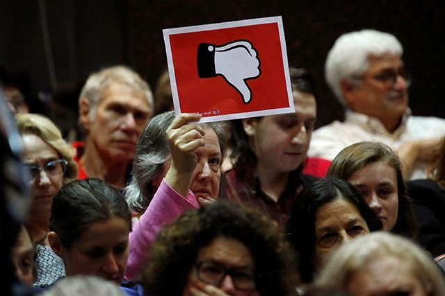 Woman holds up a sign at a congressional town hall meeting