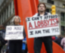 "An occupy wallstreet protestor holds up a sign that says ""I can't afford a lobbyist, I am the 99%"""
