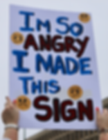 An Advocate Holds up a sign about being angry with government, but powerles to change it. Signing up for The Advocacy Guide helps people learn how to influnce Congress and their elected representatives