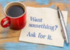 "Cup of coffee sitting on top of a napkin that says, ""Want Something? Ask for it."""