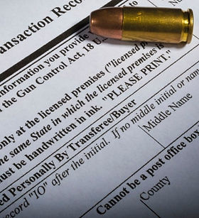A background check form needed to purchase a firearm with a bullet sitting on top