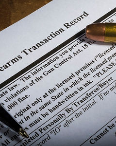 Background check form laying on a table with a bullet over the Gun Control Act section