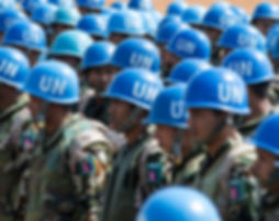 United Nations Peacekeepers stand in attendance in a conflict zone