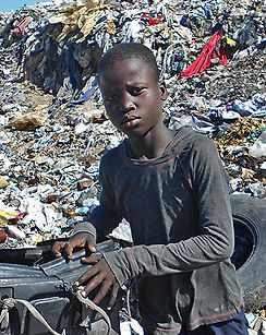 A young Haitian sits in front of a pile of trash in Haiti