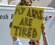 A man holds up an ironic sign that says, My Arms Are Tired, at a political protest
