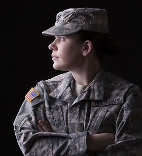 Female soilder in military uniform stares off into the distance against a black background
