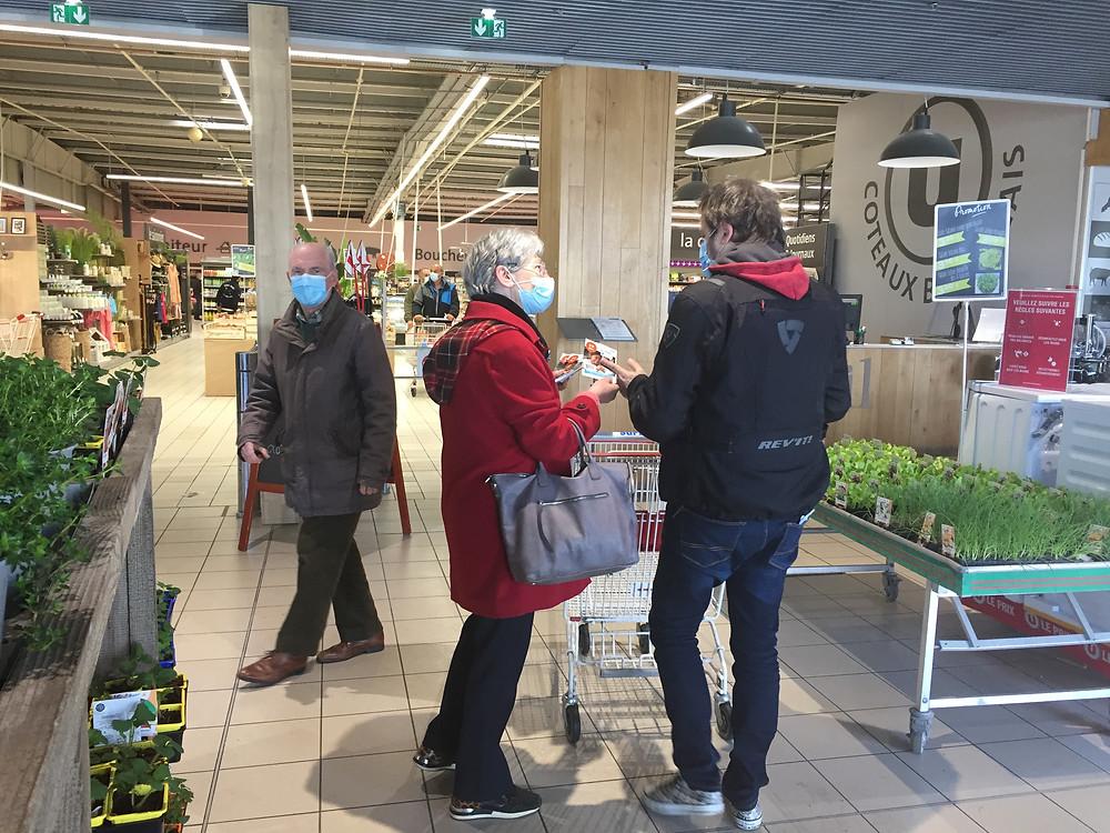 Une bénévole de PSE Aquitaine propose le flyer à l'entrée du magasin