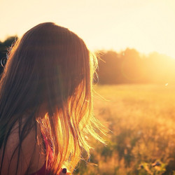 young-woman-standing-in-meadow-looking-at-trees-at-sunset_edited