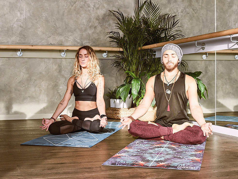 Man and woman sitting in relaxed poses on yoga mat during a retreat