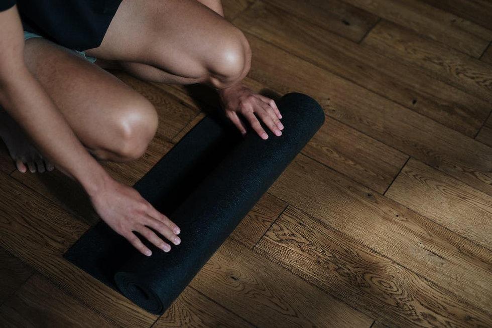 Detail of student unrolling yoga mat on stuio floor