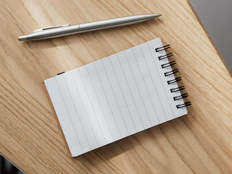 Reporter's notepad and stainless steel pen on wooden desk top