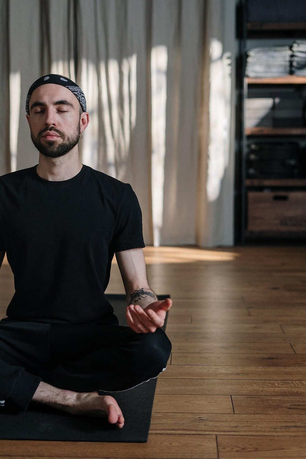 Young beareded man sittin in relaxed yoga pose